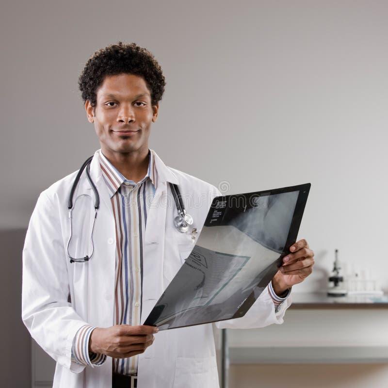 Capa del laboratorio del doctor que desgasta que examina la radiografía médica foto de archivo