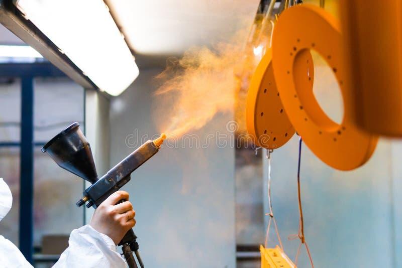 Capa del polvo de piezas de metal Una mujer en un traje protector rocía la pintura del polvo de un arma en productos de metal imagen de archivo