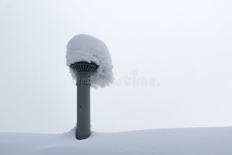 Capa enorme de nieve en el tejado y el tubo de la ventilación imagenes de archivo