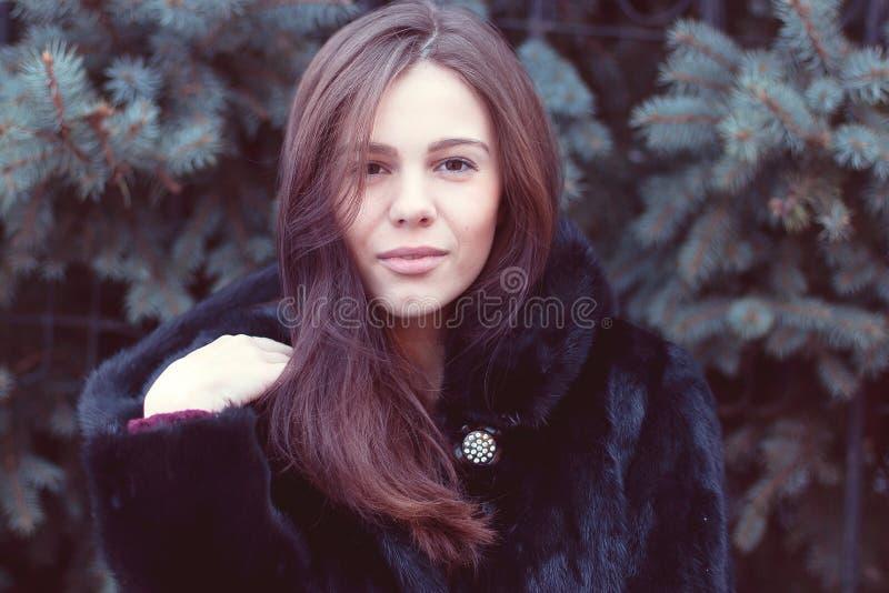 Capa morena de ojos marrones hermosa del negro del invierno de la muchacha que presenta los árboles del fondo, idea del concepto  foto de archivo libre de regalías