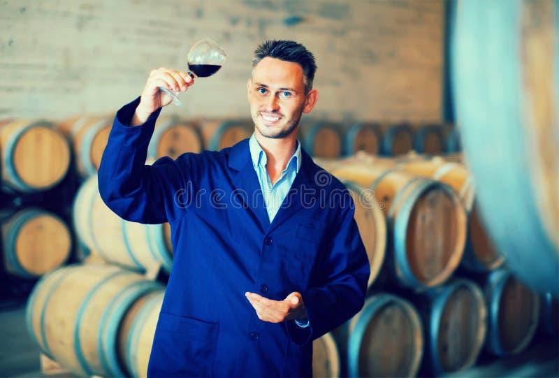 Capa que lleva experta del lagar que sostiene el vidrio de vino imágenes de archivo libres de regalías