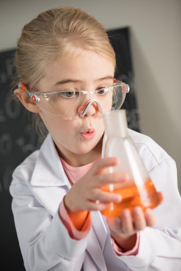 Capa salida del laboratorio de la muchacha que lleva y vidrios protectores que sostienen el frasco con el reactivo anaranjado imagenes de archivo