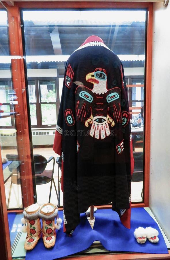 Capa tribal, deslizadores y botas del nativo americano de Alaska imagenes de archivo