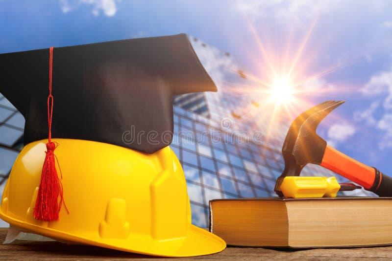 Capacete amarelo com o chapéu do estudante em de madeira imagem de stock