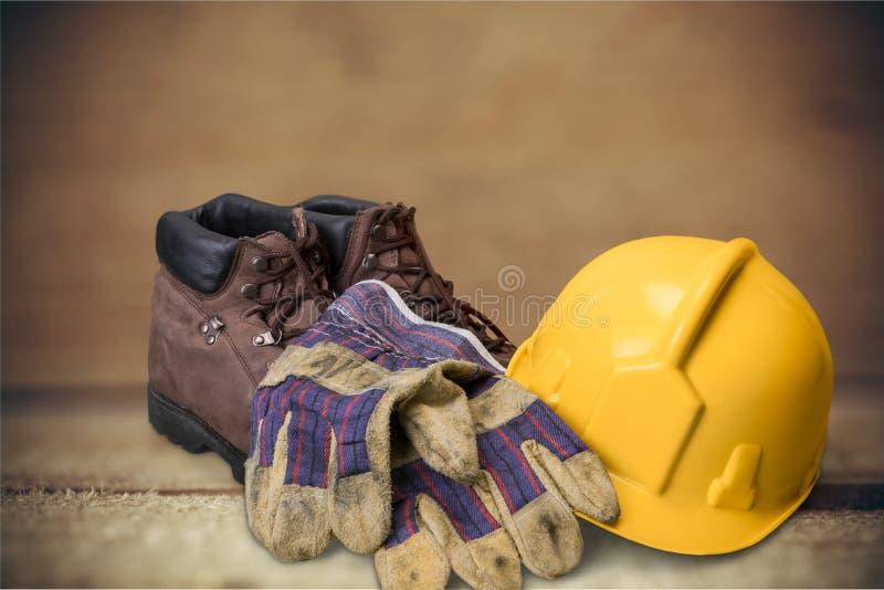 Capacete amarelo, luvas com as botas em de madeira foto de stock royalty free
