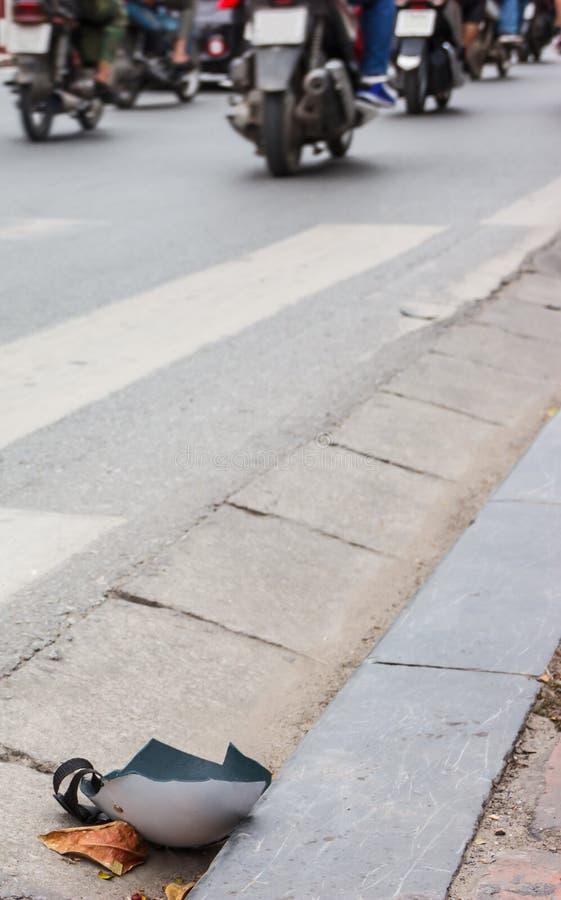 Capacete danificado quebrado na estrada carro, impacto da bicicleta, acidente, perda e seguro, conceito da chamada do hospital fotografia de stock
