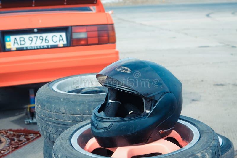 Capacete de competência preto que descansa em uma pilha de pneus usados na competição 09 da tração de Vinnytsia 07 2017, foto edi fotografia de stock royalty free