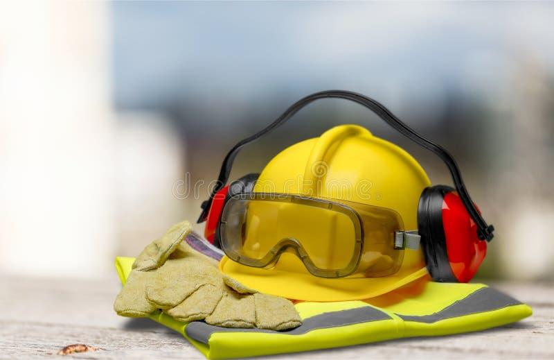 Capacete de segurança com fones de ouvido e óculos de proteção sobre fotografia de stock royalty free