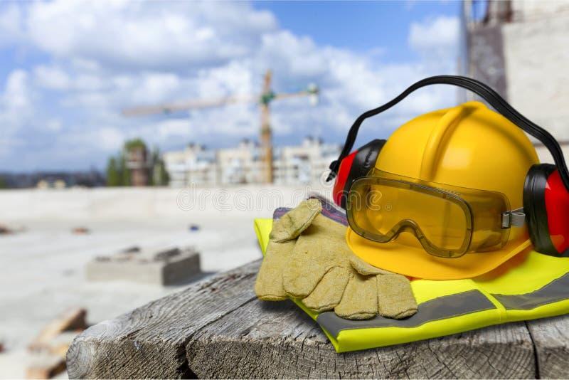 Capacete de segurança com fones de ouvido e óculos de proteção sobre foto de stock