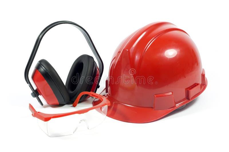 Capacete de segurança vermelho do workwear protetor, óculos de proteção transparentes com quadro vermelho e capas protetoras para foto de stock