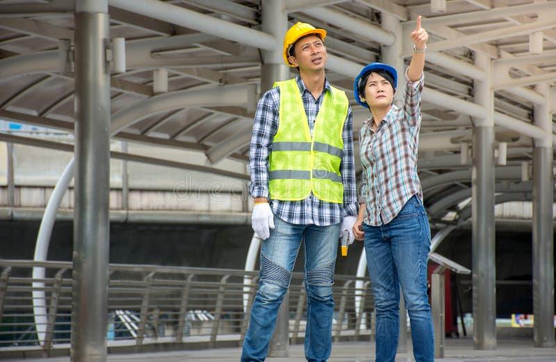 Capacete de segurança vestindo da equipe asiática profissional da engenharia que fala sobre o projeto de construção e que aponta  fotos de stock