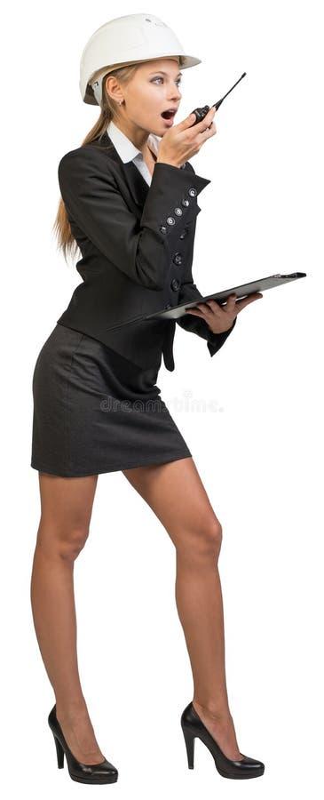 Capacete de segurança vestindo da mulher de negócios, guardando a prancheta imagem de stock royalty free