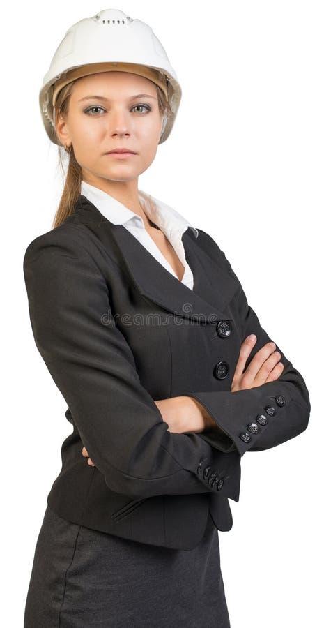 Capacete de segurança vestindo da mulher de negócios, seus braços cruzados foto de stock