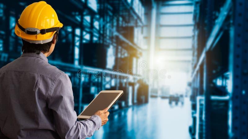 Capacete de segurança de Wearing do gerente do coordenador usando a verificação e o controle da tabuleta para trabalhadores fotografia de stock