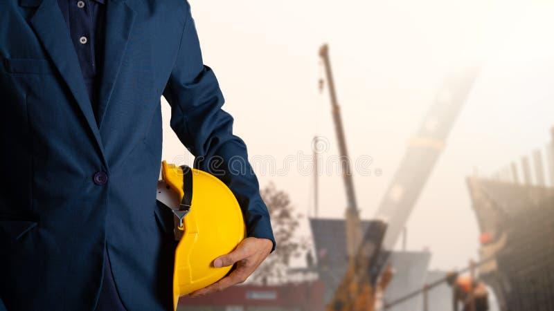 Capacete do amarelo da posse do coordenador ou do trabalhador para a segurança dos trabalhadores foto de stock