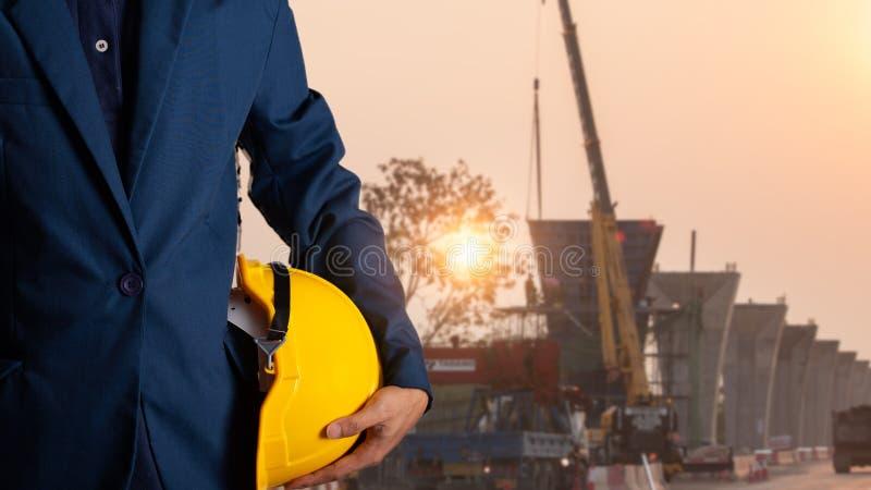 Capacete do amarelo da posse do coordenador ou do trabalhador para a segurança dos trabalhadores fotos de stock