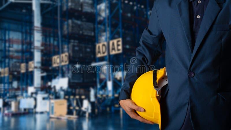 Capacete do amarelo da posse do coordenador ou do trabalhador para a segurança dos trabalhadores com o armazém de comércio modern imagens de stock royalty free