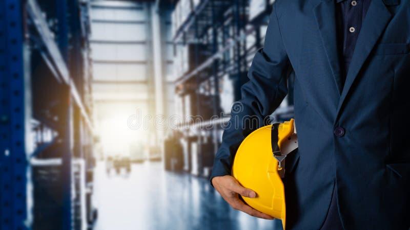 Capacete do amarelo da posse do coordenador ou do trabalhador para a segurança dos trabalhadores com o armazém de comércio modern foto de stock royalty free