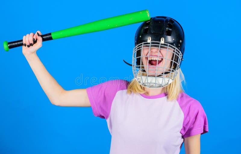 Capacete do basebol do desgaste da menina e bastão louros bonitos da posse no fundo azul Bata sua cabeça com bastão Conceito mudo imagens de stock