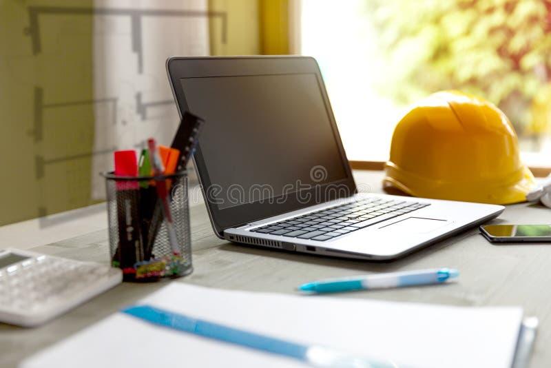 Capacete do portátil e dos contratantes no escritório dos desenhistas/arquitetos fotos de stock royalty free
