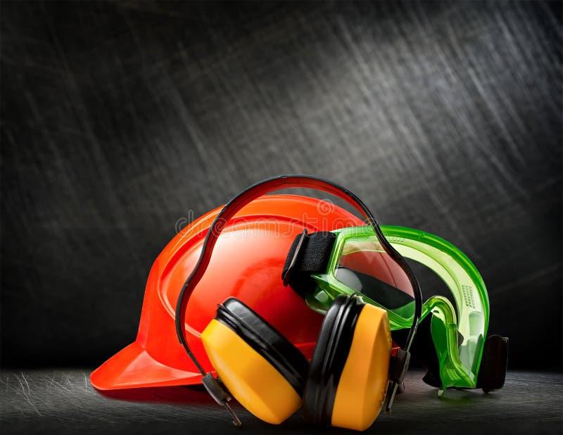 Capacete vermelho com fones de ouvido e óculos de proteção fotografia de stock royalty free