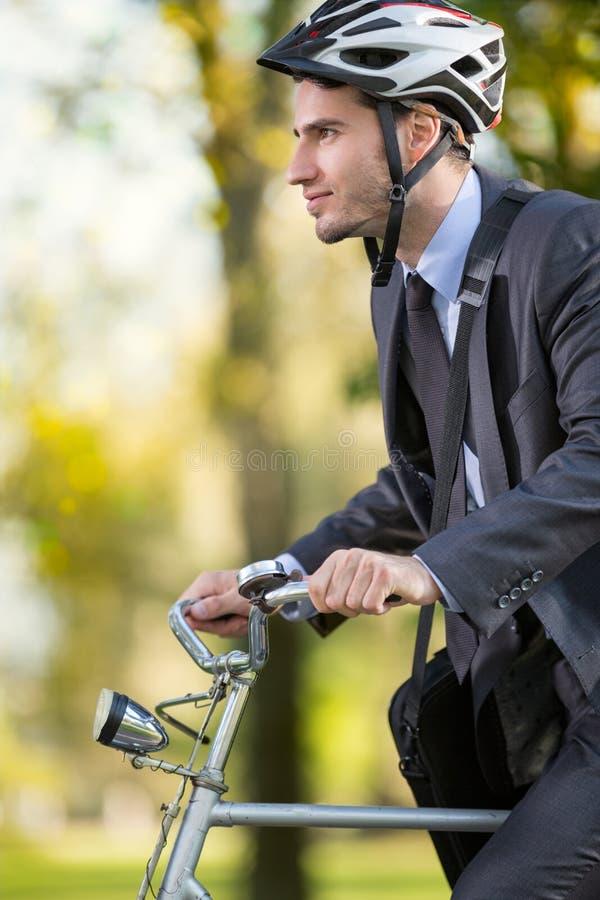 Capacete vestindo da bicicleta do homem de negócios novo imagens de stock
