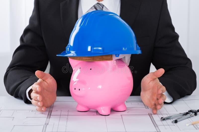 Capacete vestindo da construção de Hands Protecting Piggybank do arquiteto fotos de stock royalty free