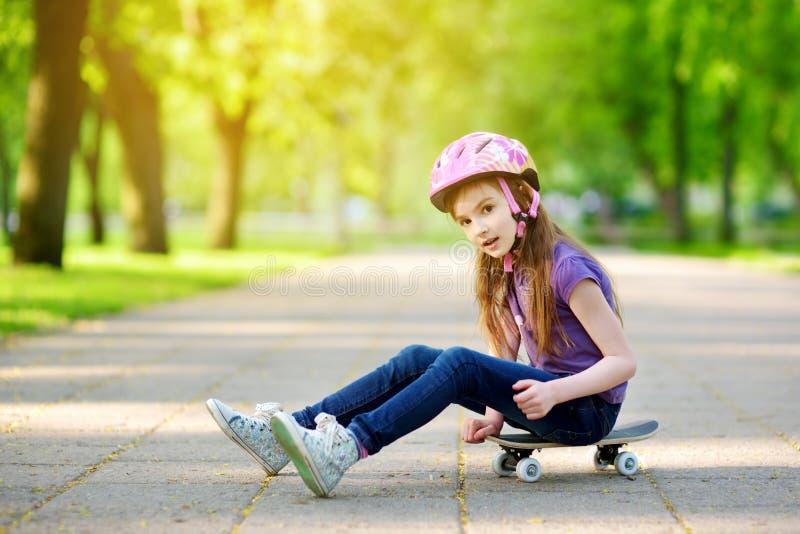 Capacete vestindo da menina pequena bonito do preteen que senta-se em um skate foto de stock royalty free