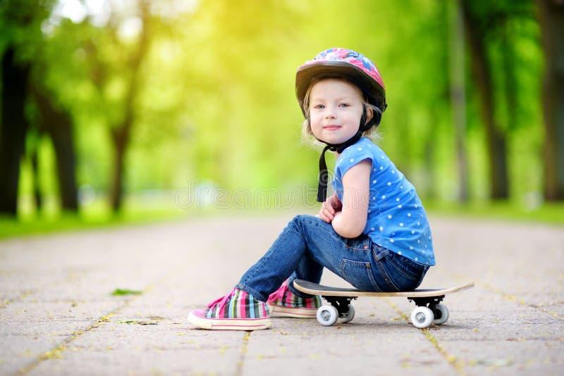 Capacete vestindo da menina pequena bonito do preteen que senta-se em um skate imagens de stock