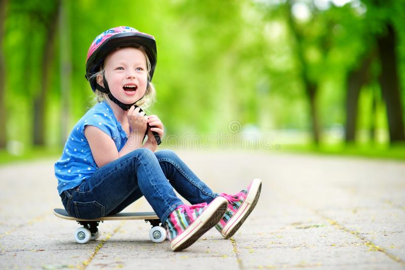 Capacete vestindo da menina pequena bonito do preteen que senta-se em um skate fotografia de stock royalty free