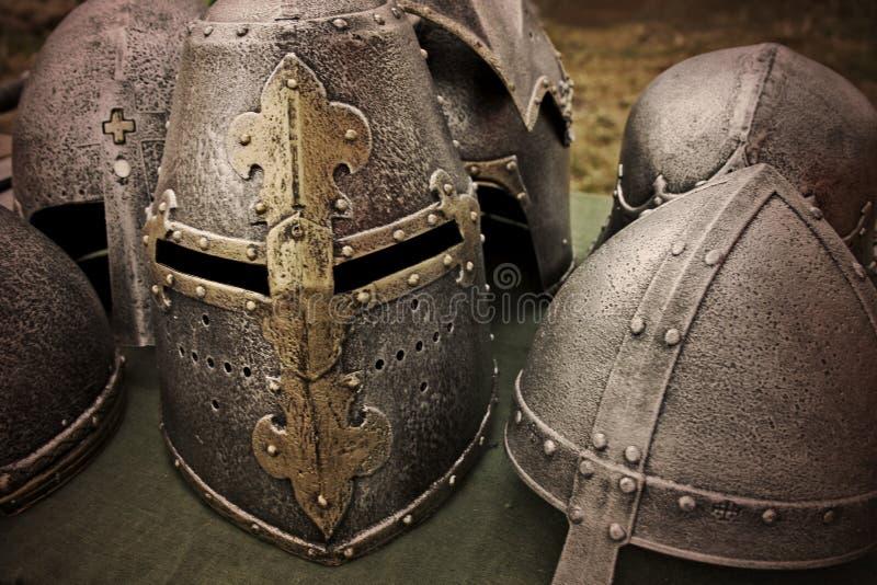 Capacetes antigos do cavaleiro na tabela imagens de stock