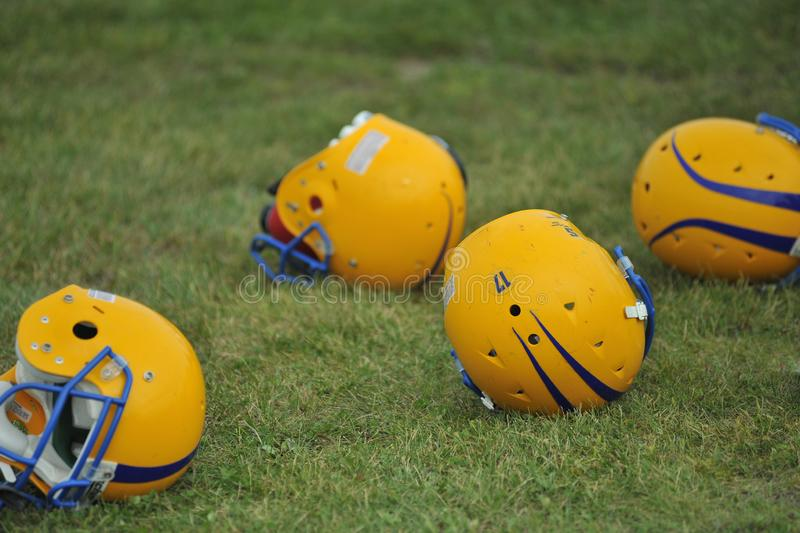 Capacetes de futebol americano na grama foto de stock royalty free