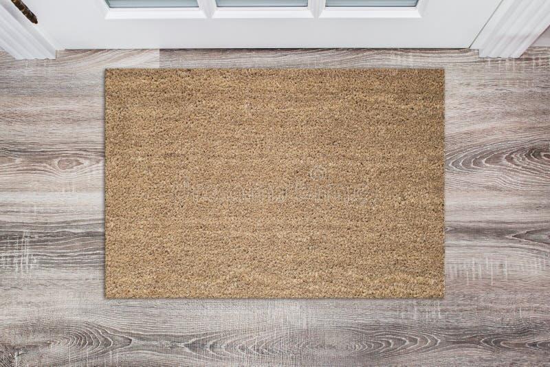 Capacho colorido bronzeado da fibra de coco da placa antes da porta branca no salão Esteira no assoalho de madeira, modelo do pro fotos de stock royalty free
