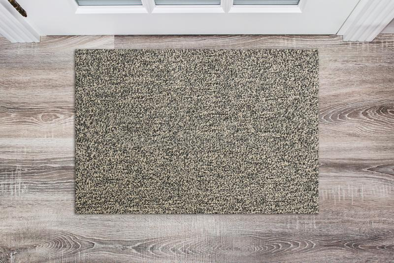 Capacho de lã bege vazio antes da porta branca no salão Esteira no assoalho de madeira, modelo do produto imagens de stock royalty free