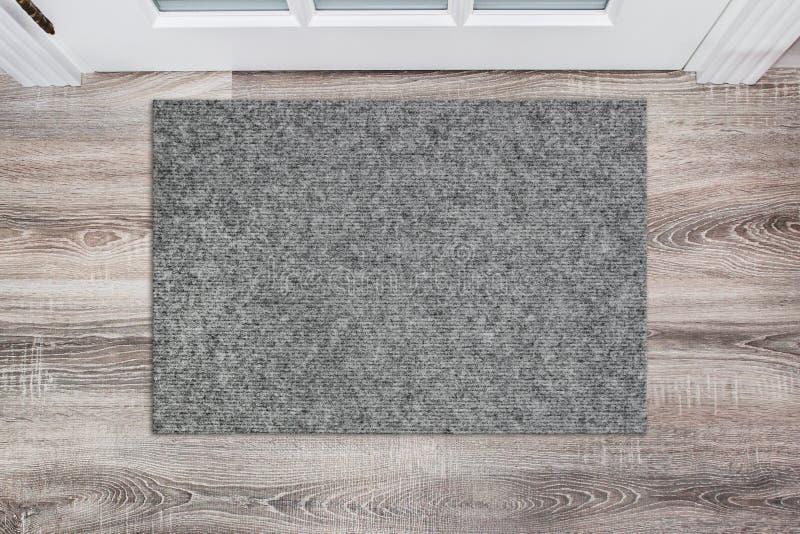 Capacho de lã cinzento vazio antes da porta branca no salão Esteira no assoalho de madeira, modelo do produto fotos de stock royalty free