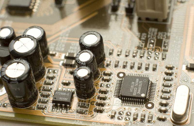 Capacitors and microchips on circuit board royalty free stock photos
