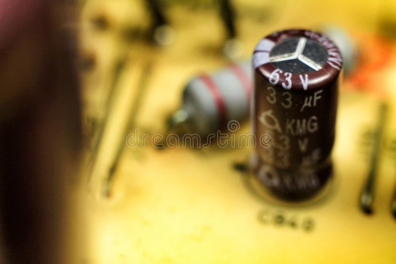 Capacitors and other components in an electronic board. Macro photography of capacitors and other electronic components in an electronic board information tech stock photos