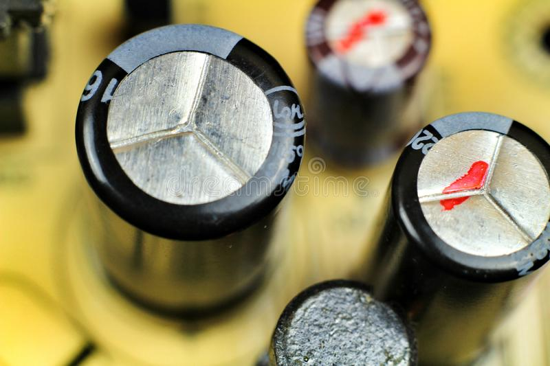 Capacitors and other components in an electronic board. Macro photography of capacitors and other electronic components in an electronic board information tech royalty free stock image