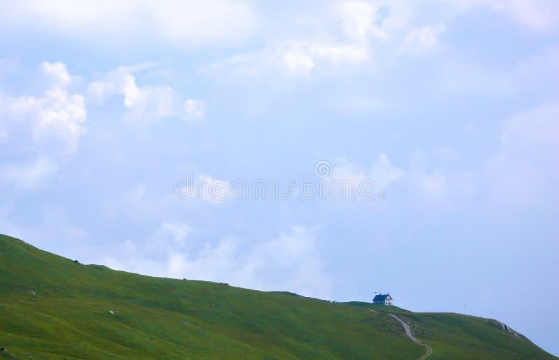 Capanna da solo isolata della montagna su un pendio di collina verde fertile del prato sotto un cielo blu espansivo nelle alpi de immagini stock