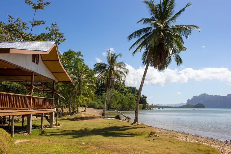 Capanna di legno sulla spiaggia tropicale con le palme e le isole su fondo Casa orientale in bella laguna Vacanza di estate Viagg fotografie stock