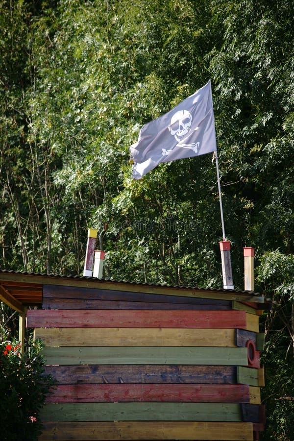 Capanna sugli'alberi con la bandiera di pirata fotografia stock