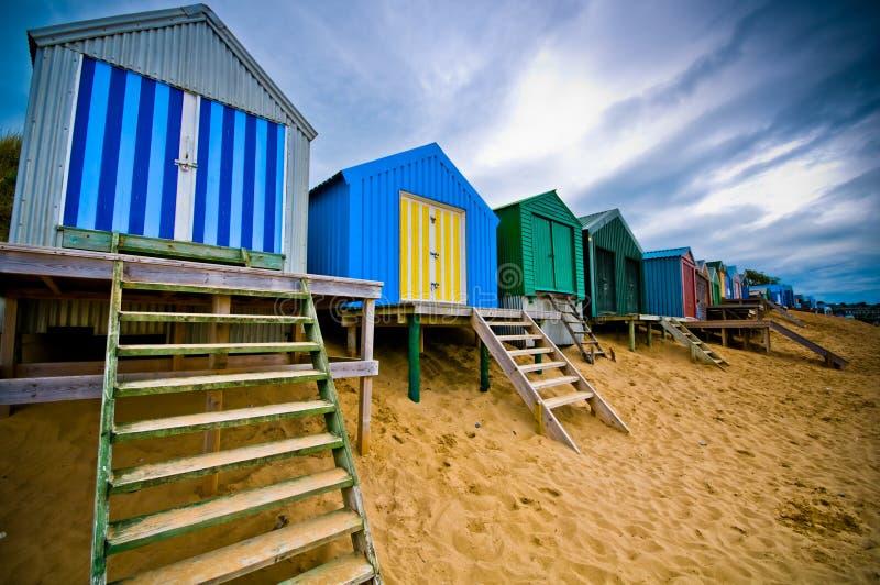 Capanne Colourful della spiaggia con il cielo drammatico fotografie stock libere da diritti