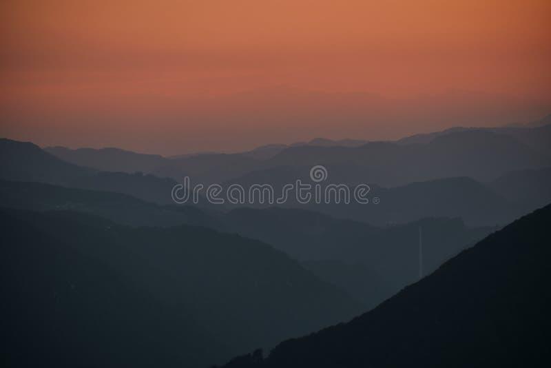 Capas de colinas en la puesta del sol con la chimenea de Trbovlje foto de archivo