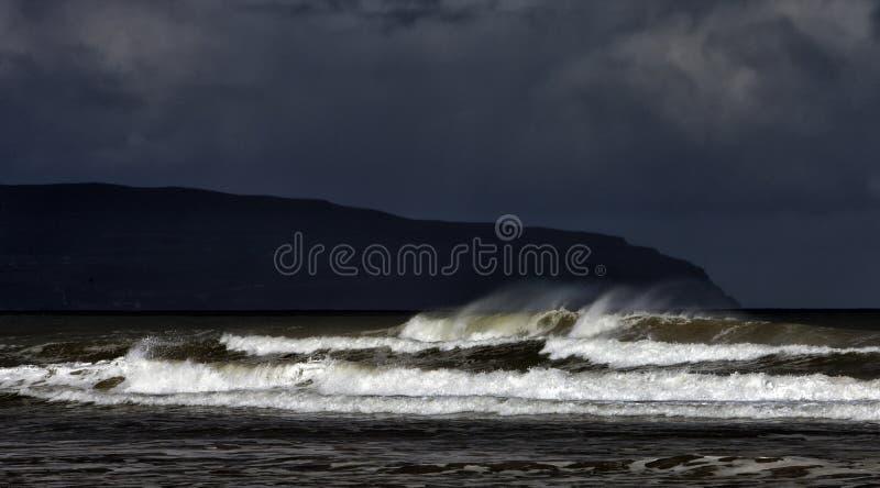 Capas de una marea y de una tormenta entrantes en la playa en declive en la heredad en declive en el condado Londonderry en Irlan foto de archivo
