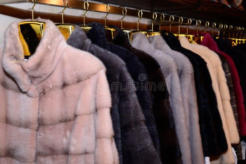Capas de visión de lujo Gris, marrón, abrigos de pieles del color de la perla en el escaparate del mercado outerwear Cierre para  imágenes de archivo libres de regalías