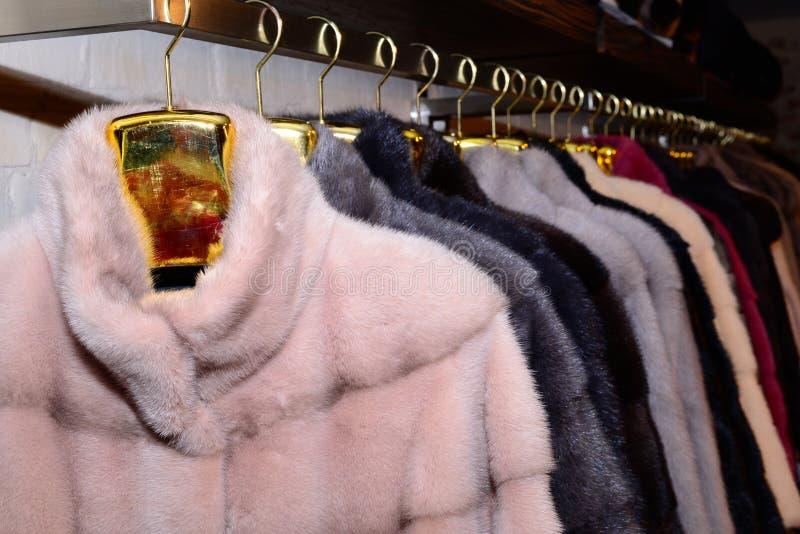 Capas de visión de lujo Gris, marrón, perla, abrigos de pieles rosados del color en el escaparate del mercado fotografía de archivo