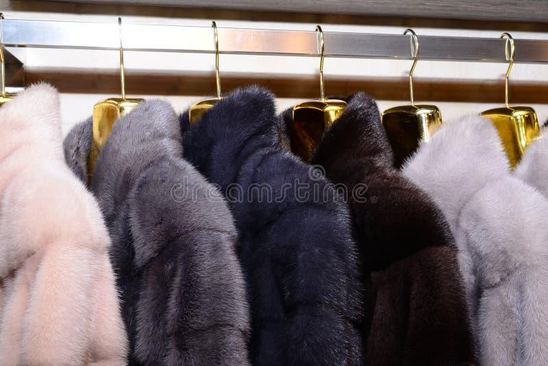 Capas de visión de lujo Rosado, gris, gris oscuro, abrigos de pieles del color de la perla en el escaparate del mercado foto de archivo