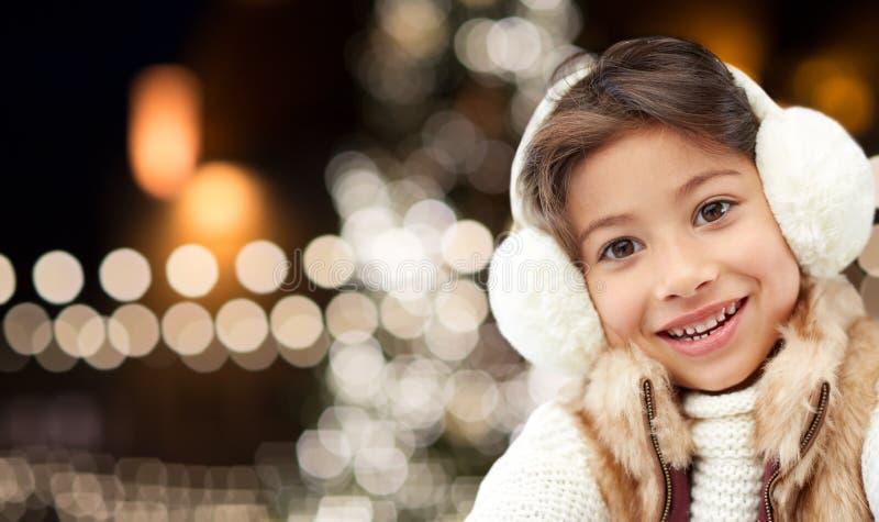 Capas protetoras para as orelhas vestindo da menina feliz sobre luzes de Natal imagens de stock royalty free