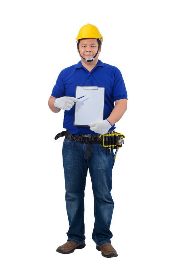 Capataz de la construcción en la camisa azul con los guantes protectores, casco con el tablero y la presentación de la tenencia d fotografía de archivo libre de regalías