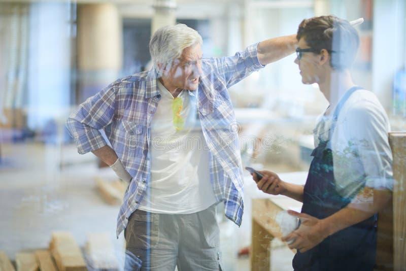 Capataz furioso del carpintero que grita en el trabajador perezoso foto de archivo libre de regalías